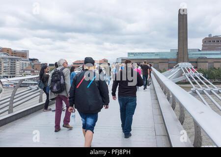 Pedestrians walking across Millennium Bridge in London looking towards the Tate Modern on Bankside - Stock Photo