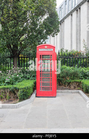 Red british phone box in St Paul's Churchyard in the City of London - Stock Photo