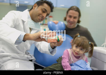 Dentist showing girl how to brush teeth using a set of false teeth, father watching in the background, close-up - Stock Photo