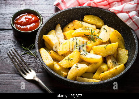 Baked potato with herbs in the pan. - Stock Photo