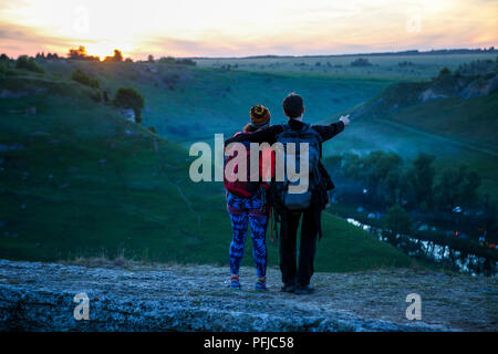 Photo from back of hugging man and tourist woman with backpacks on mountain - Stock Photo