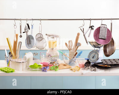 Various cooking and baking utensils on shelf and hanging from rail - Stock Photo