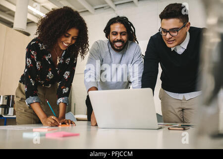 Businessmen and woman working on a laptop together as a team. Woman entrepreneur making notes during a discussion with colleagues in office. Stock Photo