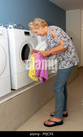 Elderly woamn removing dried clothing from a drier machine in a laundry room - Stock Photo