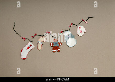 Homemade Christmas decorations tied to piece of string - Stock Photo