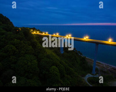 Drone view of the illuminated Zubova Schel viaduct and mountainside with forest on the background of the sea at dusk, Sochi, Russia - Stock Photo