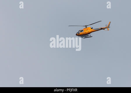 Helicopter flying over shoreham by sea coastal area. Image taken with 150-600 sigma lens while photographing waders. Vertical lift off and hovering. - Stock Photo