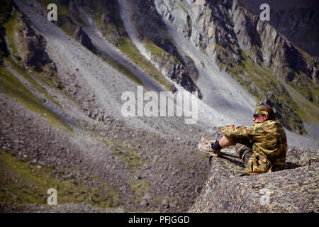 Young man sits on a stone watching panorama of Altai mountains in Russia - Stock Photo