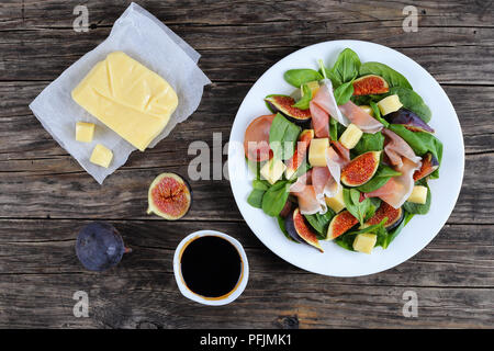 spinach, figs, thinly sliced italian ham and mozzarella cheese salad on white plate on dark wooden kitchen table with piece of cheese on paper and bal - Stock Photo