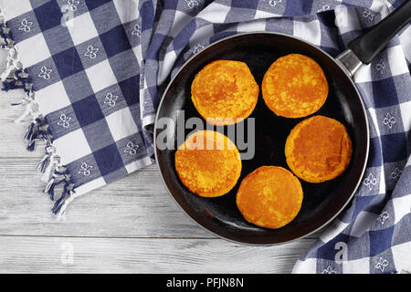 delicious golden yellow pumpkin pancakes on skillet on wooden table with kitchen towel, view from above - Stock Photo