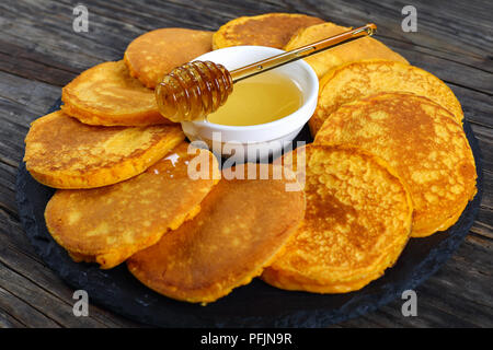 delicious golden yellow pumpkin pancakes on black stone plate with honey in center on dark wooden table, view from above, close-up - Stock Photo