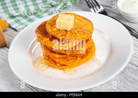 stack of pumpkin pancakes topped with piece of butter and pour over with honey on white plate on kitchen tablecloth, view from above - Stock Photo
