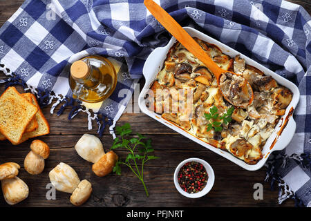 Sliced mushrooms cooked with sour cream,  onion and butter in baking dish on old wooden table, bottle of olive oil, raw mushrooms, toasted bread on ba - Stock Photo