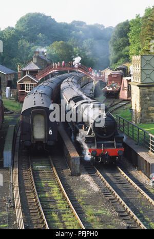Great Britain, England, North Yorkshire, two steam trains passing each other, footbridge overhead - Stock Photo