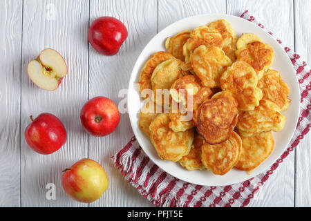 homemade Apple Greek Yogurt Pancakes - thick, fluffy and loaded with juicy pieces of fruits, on white plate with apples at background, view from above - Stock Photo