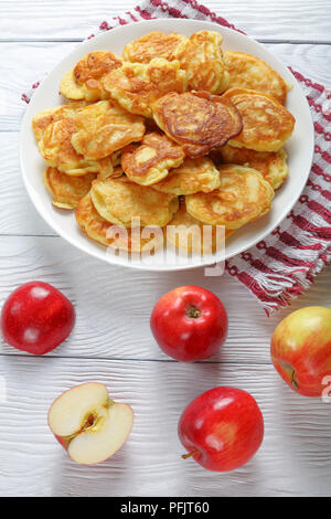 Apple Greek Yogurt Pancakes - thick, fluffy and loaded with juicy pieces of fruits, on white plate with apples at background, easy morning recipe, ver - Stock Photo