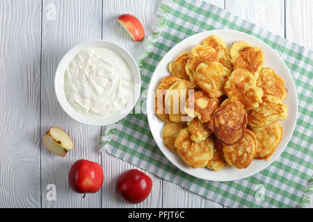delicious Apple Greek Yogurt Pancakes - thick, fluffy and loaded with juicy pieces of fruits, on white plate on kitchen table with bowl of fresh homem - Stock Photo