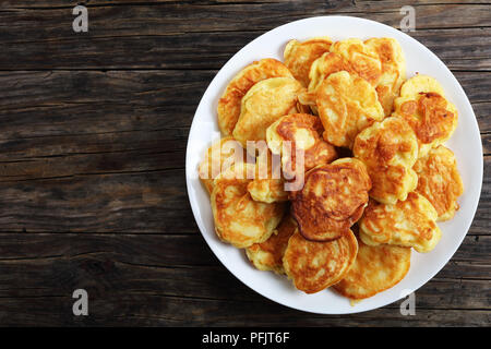 delicious Apple Greek Yogurt Pancakes - thick, fluffy and loaded with juicy pieces of fruits, on white plate on old dark wooden table, view from above - Stock Photo
