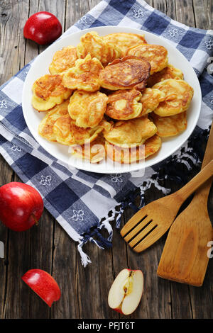 delicious Pancakes loaded with juicy pieces of apple, on white plate on old dark wooden table with spatulas and apples at background, vertical view fr - Stock Photo