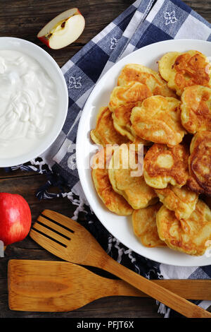 delicious Pancakes loaded with juicy pieces of apple, on white plate on old dark wooden table with sour cream in bowl and apples at background, vertic - Stock Photo