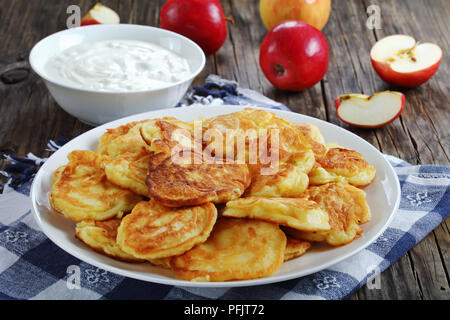 delicious homemade Pancakes loaded with juicy pieces of apple, on white plate on old dark wooden table with sour cream in bowl and apples at backgroun - Stock Photo