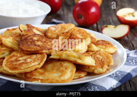 tasty fluffy Pancakes loaded with juicy pieces of apple, on white plate on old dark wooden table with sour cream in bowl and apples at background, sid - Stock Photo