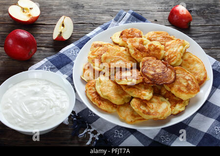 tasty fluffy Pancakes loaded with juicy pieces of apple, on white plate on kitchen towel with sour cream in bowl and apples on old wooden table, view  - Stock Photo