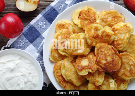 close-up of tasty fluffy Pancakes loaded with juicy pieces of apple, on white plate on kitchen towel with sour cream in bowl and apples on old wooden  - Stock Photo