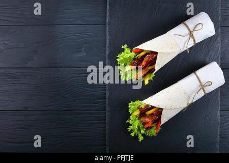 delicious freshly made sandwich wraps with frisee lettuce, sweet peppers, coleslaw and fried chicken sticks on black stone tray, view from above - Stock Photo