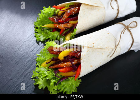 close-up of delicious freshly made sandwich wraps with frisee lettuce, sweet peppers, coleslaw and fried chicken sticks on black stone tray, view from - Stock Photo