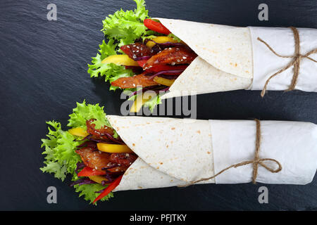 close-up of delicious fresh juicy flatbread sandwich wraps with frisee lettuce, sweet peppers, coleslaw and fried chicken meats on black stone tray, v - Stock Photo