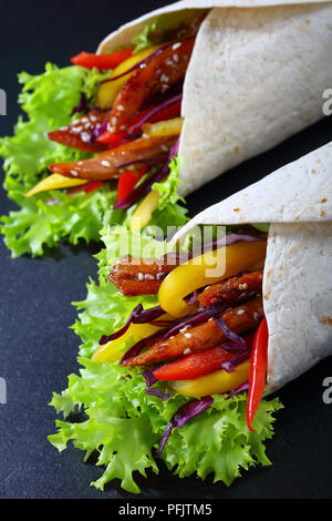 close-up of delicious fresh juicy flatbread sandwich wraps with frisee lettuce vegetables salad and  fried spicy chicken fillet on black stone tray, v - Stock Photo
