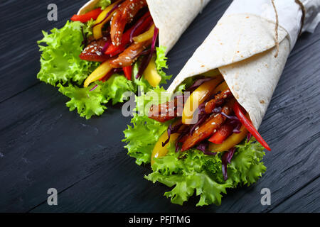close-up of delicious fresh juicy flatbread sandwich wraps with frisee lettuce vegetables salad and  fried spicy chicken fillet on black wooden boards - Stock Photo