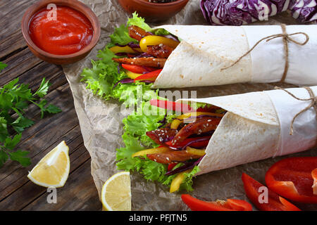 close-up of delicious freshly made sandwich wraps with frisee lettuce, sweet peppers, coleslaw and fried honey glazed chicken sticks on paper. ingredi - Stock Photo