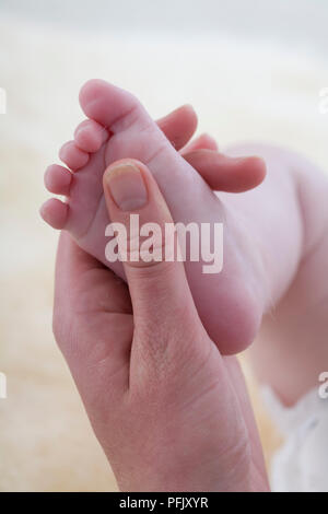 Woman's hand massaging baby's foot, close-up - Stock Photo