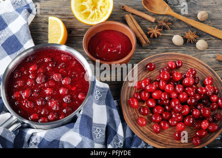 delicious cranberry sauce in saucepan and in bowl on wooden table with fresh cranberry on plate and ingredients at background, authentic recipe, horiz - Stock Photo