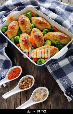 delicious roasted in oven fish cutlets with steamed carrots, onion, brussel sprouts in baking dish on dark wooden table, with kitchen towel and spices - Stock Photo