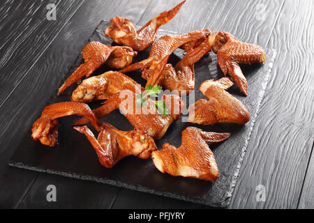 delicious crispy smoked chicken wings on a black stone plate on wooden table, view from above - Stock Photo