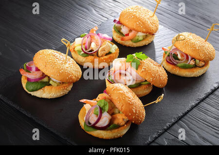 delicious grilled burgers pinned with bamboo skewers or pinchos with seafood, red onion and greens on black slate tray on wooden table, spain cuisine, - Stock Photo