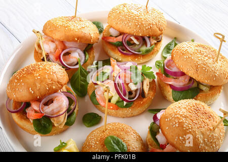 delicious grilled juicy burgers pinned with bamboo skewers or pinchos with seafood, red onion and greens on white platter on wooden table, spain cuisi - Stock Photo