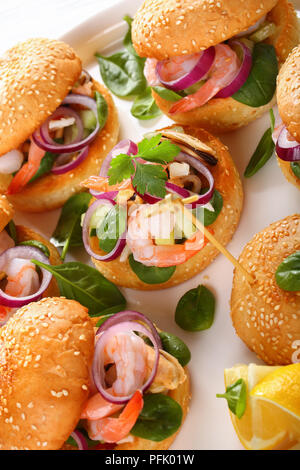 grilled juicy burgers pinned with bamboo skewers or pinchos with seafood - shrimps, mussels, squid strips, red onion and spinach on white dish on wood - Stock Photo