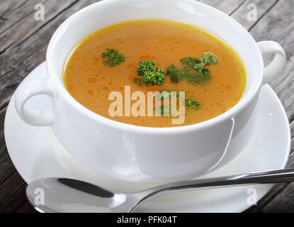 close-up of delicious Chicken broth in a white soup cup with spoon, view from above - Stock Photo