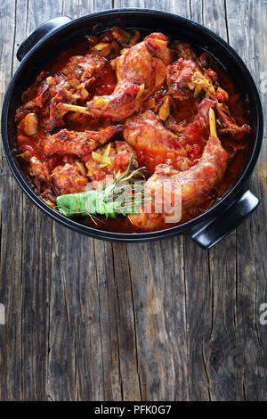 Italian Style Braised Rabbit With leek, chopped tomatoes, herbs and mushrooms in dutch oven on old dark wooden table, vertical view from above - Stock Photo