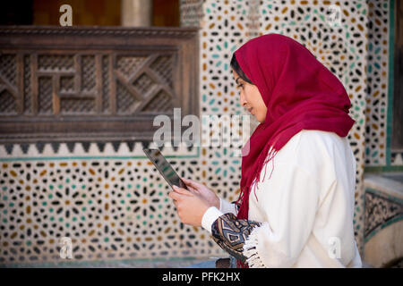 Muslim woman working on tablet in traditional clothing with red headscarf on her head beside a traditional arabesque Moroccan wall - Stock Photo