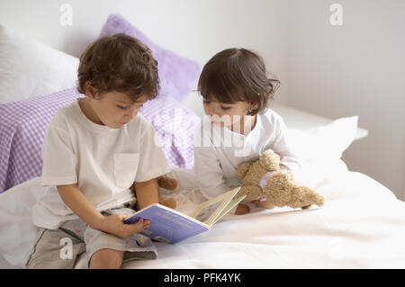 Young boy in pyjamas reading book to young girl lying in bed with teddy bear and toy rabbit - Stock Photo