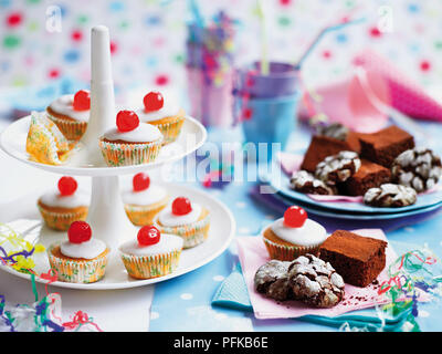 Fairy cakes, chocolate brownies and chocolate crinkle cookies arranged on a cakestand, on napkins and on plates, cups and drinking straws in background - Stock Photo