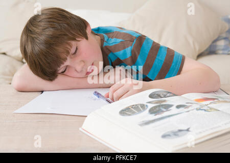 Boy fallen asleep over his homework, lying on bed with textbook open, head resting on arm, close-up, front view - Stock Photo