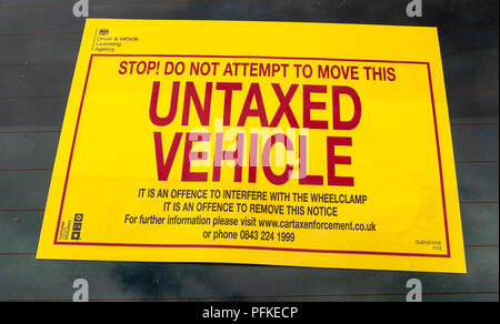 A Untaxed Vehicle notice stuck on the windscreen of an untaxed car - Stock Photo