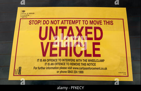 A Untaxed Vehicle notice stuck on the windscreen of a car - Stock Photo