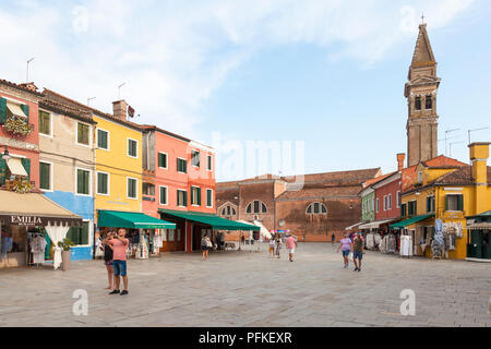 Sunset in the colourful fishing village on Burano Island, Venice, Veneto, Italy. Via Baldassare Galuppi, the main street, with shops, tourists and res - Stock Photo